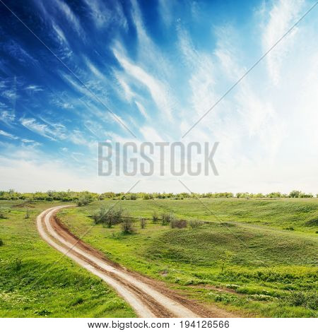 road in green meadow and sunset in deep blue sky