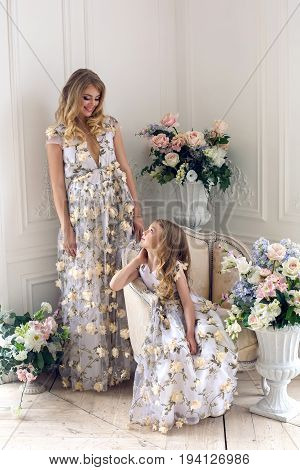mother and daughter are in the same floral dresses in the studio