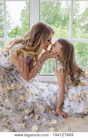 mother kissing daughter in matching dresses sitting by the large window on the floor of the house