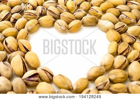 Pistachios on a white background.The heart is lined with pistachio