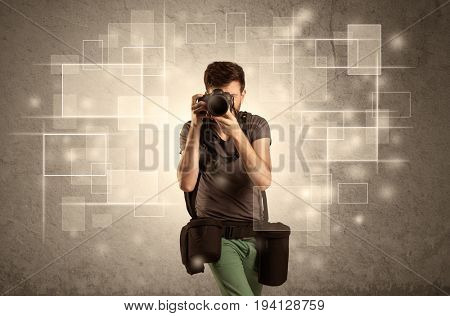 A hobby photographer with professional camera gear and belt shooting in front of brown sepia urban concrete wall full of glowing square illustrations concept