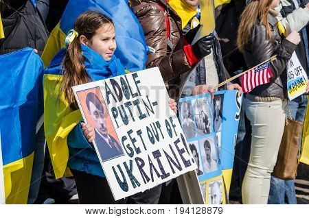 Washington DC USA - March 6 2014: Young girl holding sign of Vladimir Putin and Russia during Ukrainian protest by White House