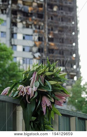 LONDON, UK - JULY 5, 2017:  A bunch of lillies placed in memory of the 80 feared killed in the Grenfell Tower block fire in Kensington North London.