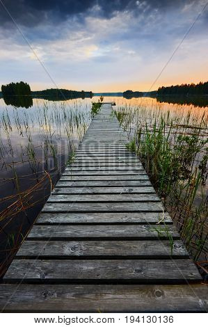 little pier at sunset in a Finnish lake under overcast sky