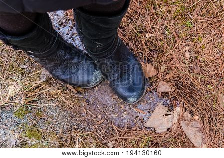 Macro closeup of frozen iced icicle on forest ground in winter with women's black leather boots