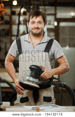 Smiling carpenter stand with eccentric grinding machine in hands at workshop. Electric device for polishing timber planks, service worker in apron at workplace