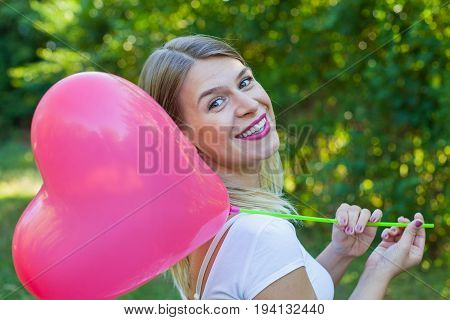 Picture of a smiling beautiful girl posing with a heart shaped helium balloon outdoor