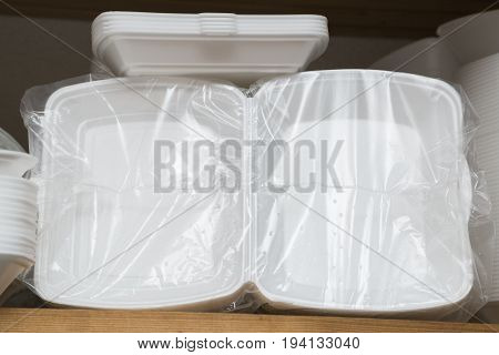 Plastic or paper white food boxes, packing or plates packed in plastic bags on a shelf for fast food in the pantry of the restaurant or cafe