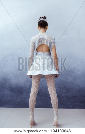 Futuristic fashion young woman. Beautiful young multi-racial asian caucasian model girl in silver urban clothes with conceptual hairstyle and make-up against textured blue wall in full lenght. Back view. Sci-fi poster style.