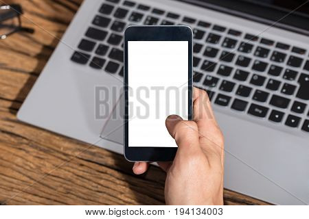 Close-up Of A Businessperson Holding Smart Phone With Blank White Screen
