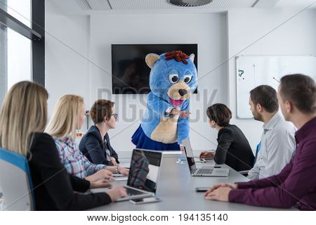 Boss dresed as teddy bear having fun with bussines people in modern corporate office