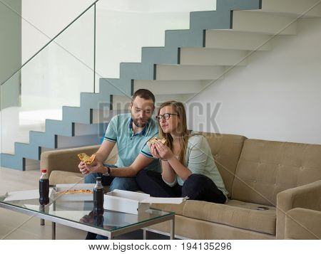 young handsome couple cheerfully spending time while eating pizza in their luxury home villa