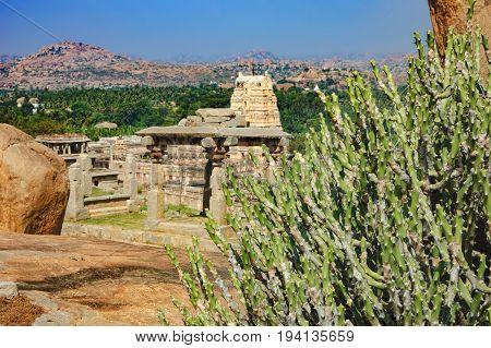 Landscape with big stones - unique mountain formation with tropical plants and ancient ruins of city Vijayanagar, Hampi, Karnataka, India.