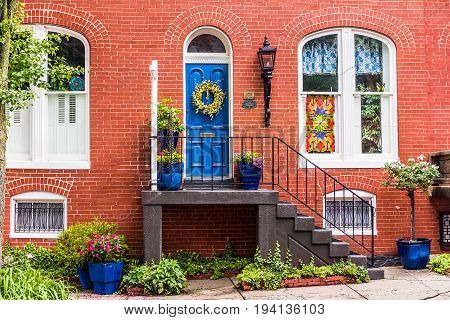 Frederick USA - May 24 2017: Residential home entrance in downtown with brick architecture and colorful porch with flowers in summer