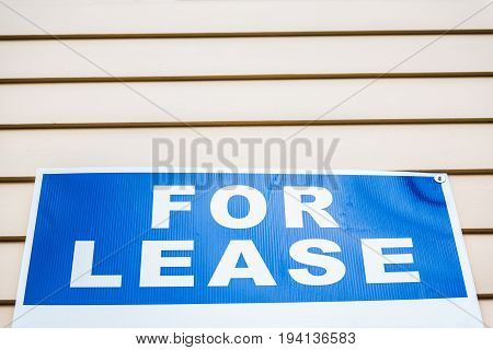 Bright blue For Lease sign macro closeup against wall