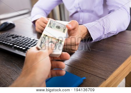 Close-up Of A Person Giving Bribe To Businessman At Workplace