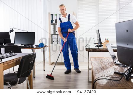 Smiling Male Janitor Cleaning Floor With Broom In Office