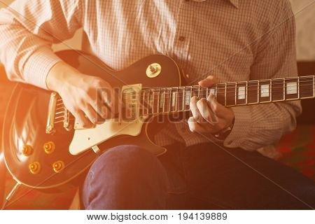 Practicing in playing guitar. Handsome young men playing guitar sunlight