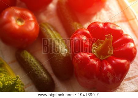 Tomatoes, cucumbers and peppers on a cutting board.