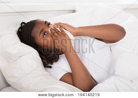 Close-up Of An African Girl Lying On Bed Blowing Her Nose With Tissue