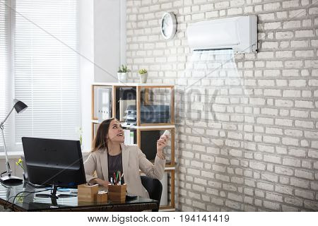 Young Businesswoman Operating Air Conditioner With Remote Controller In Office