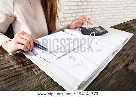 Close-up Of A Businesswoman Calculating Invoice Using Calculator At Workplace