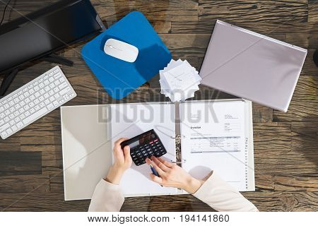 Elevated View Of A Businesswoman Calculating Invoice At Workplace