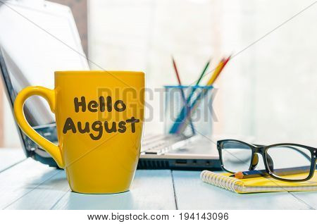 Hello August - inscription at yellow morning coffee or tea cup at business office background. Summer month, Calendar concept.