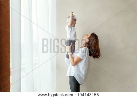 Young mother holding her young daughter. Woman and new born girl relax in a bedroom. Mother breast feeding baby. Family at home. Young mother playing whith her newborn daughter