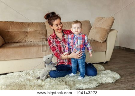 Young mother playing with her young daughter. Woman and new born girl relax in a bedroom. Mother breast feeding baby. Family at home. Young mother playing whith her newborn daughter