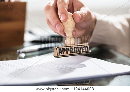 Close-up Of A Person Holding Approved Stamp On Document Over The Desk In Office