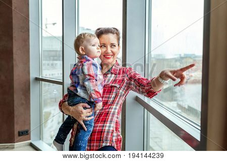 Young mother holding her young daughter. Woman and new born girl relax in a bedroom near the windiow. . Mother breast feeding baby. Family at home. Young mother playing whith her newborn daughter