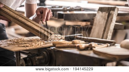 male carpenter working with a wood product hand tools close up