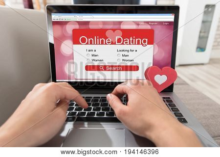 Person Using Online Dating Website On Laptop