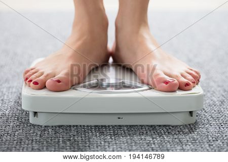Close-up Of A Woman's Feet On Weighing Scale Over The Carpet