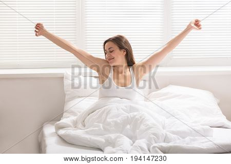 Happy Young Woman Waking Up On Bed In Morning