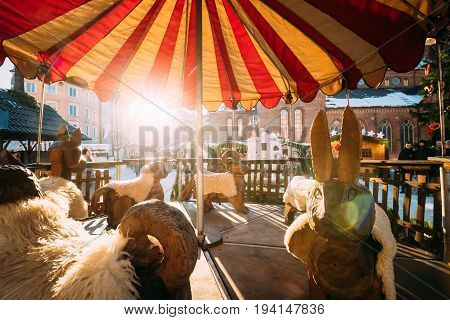 Riga, Latvia - December 1, 2016: Traditional Vintage Old Carousel Merry-go-round On Christmas Market On The Dome Square In Riga Latvia. Winter Holidays New Year In Europe. Sun Is Shining In Sunset