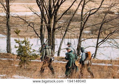 Rogachev, Belarus - February 25, 2017: Group Of Unidentified Re-enactors Dressed As German Wehrmacht Infantry Soldiers In World War II Marching Along Forest Road At Autumn Season.