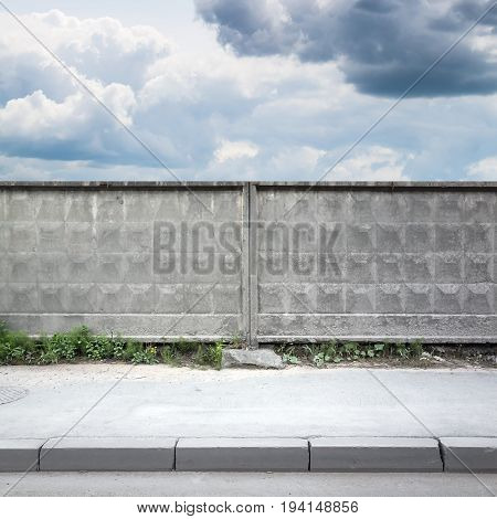 Old Gray Concrete Fence Under Cloudy Sky
