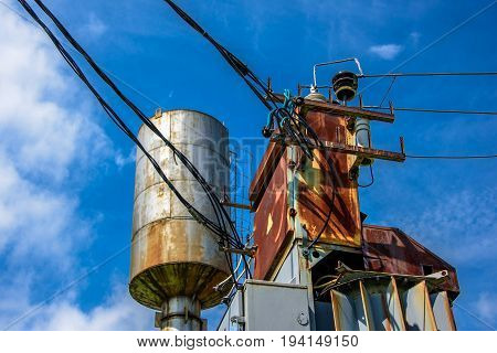 Industrial view of rusty transformer box, electrical wires and water tower with a ladder on the side on a background of blue sky with white clouds at sunny day