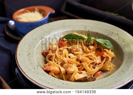 Seafood pasta. Tagliatelle with prawns and spices in tomato-cream sauce. Glass of white wine.