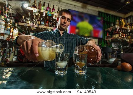 A cute barman holds bottles filling glasses