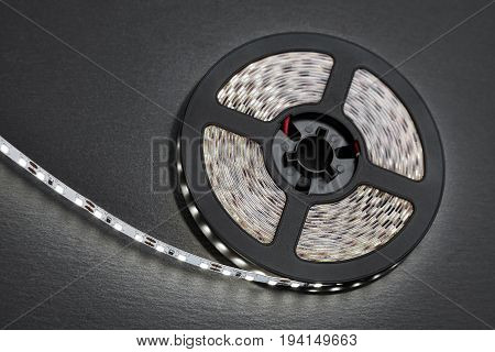 Reel of a diode strip with cold light on a stone dark background