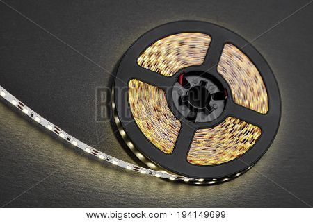 Reel of a diode strip with warm light on a stone dark background