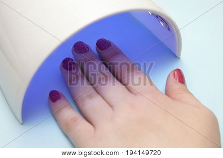 varnish on the nails the ultraviolet lamp dries the gel lacquer on the female hand