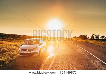 Gomel Belarus - August 25, 2016: Sun Rising Over VW Volkswagen Polo Vento Sedan Car Parking Near Asphalt Country Road In Sunny Morning Or Evening. Open Road At Sunny Sunset Or Sunrise Time At Summer