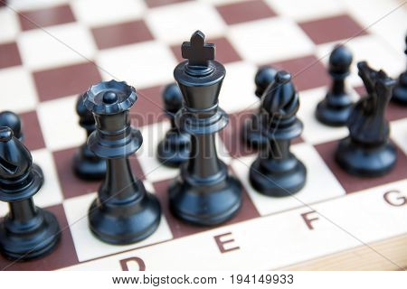 Photo of black chess pieces with selective focus on the king