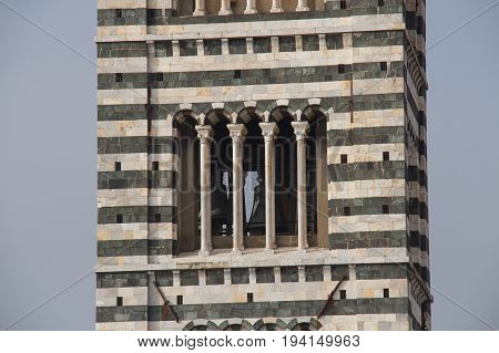 Italy Siena - December 26 2016: the close up view of the bell tower of Duomo di Siena. The view of Romanesque stylistic patterns on Campanile on December 26 2016 in Siena Tuscany Italy.