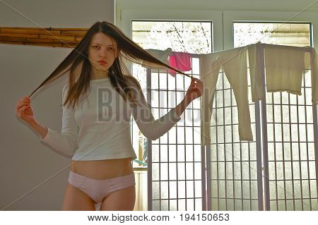 Young beautiful girl shows the photographer part of her young body looking at her reflection in the mirror