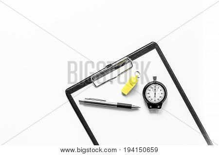 To judge competition. Stopwatch, whistle, pad on white table background top view copyspace.